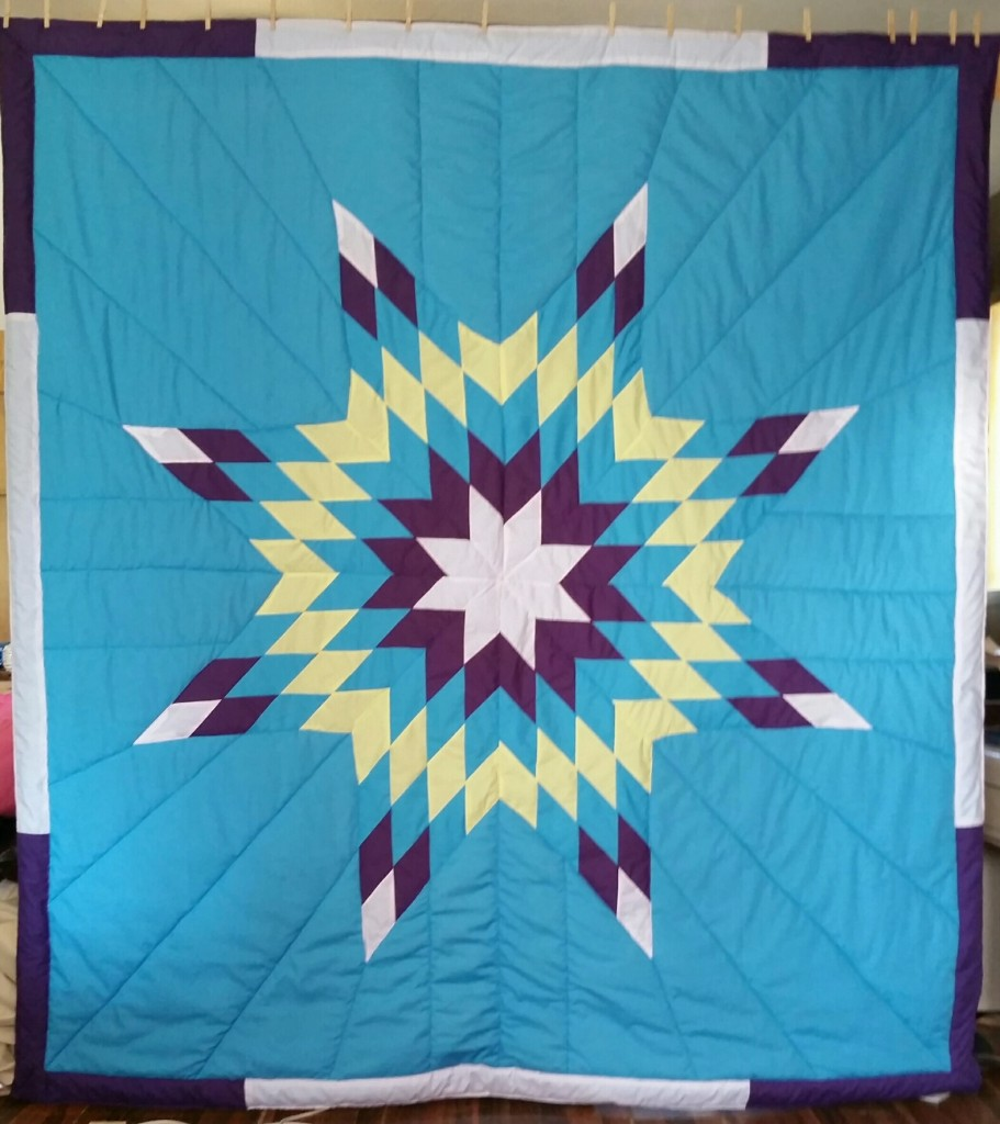 Turqoise Star Blanket with white, purple, yellow and turquoise star and border.