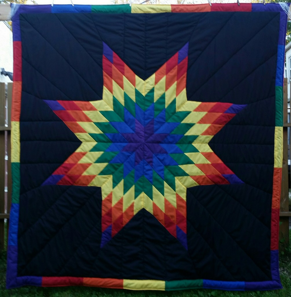 Black blanket with rainbow colors in the star (purple, blue, green, yellow, orange, red) and rainbow border
