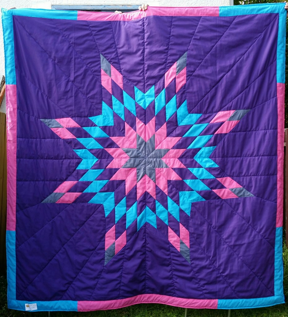Purple Star Blanket with grey, pink, purple, and turquoise star.