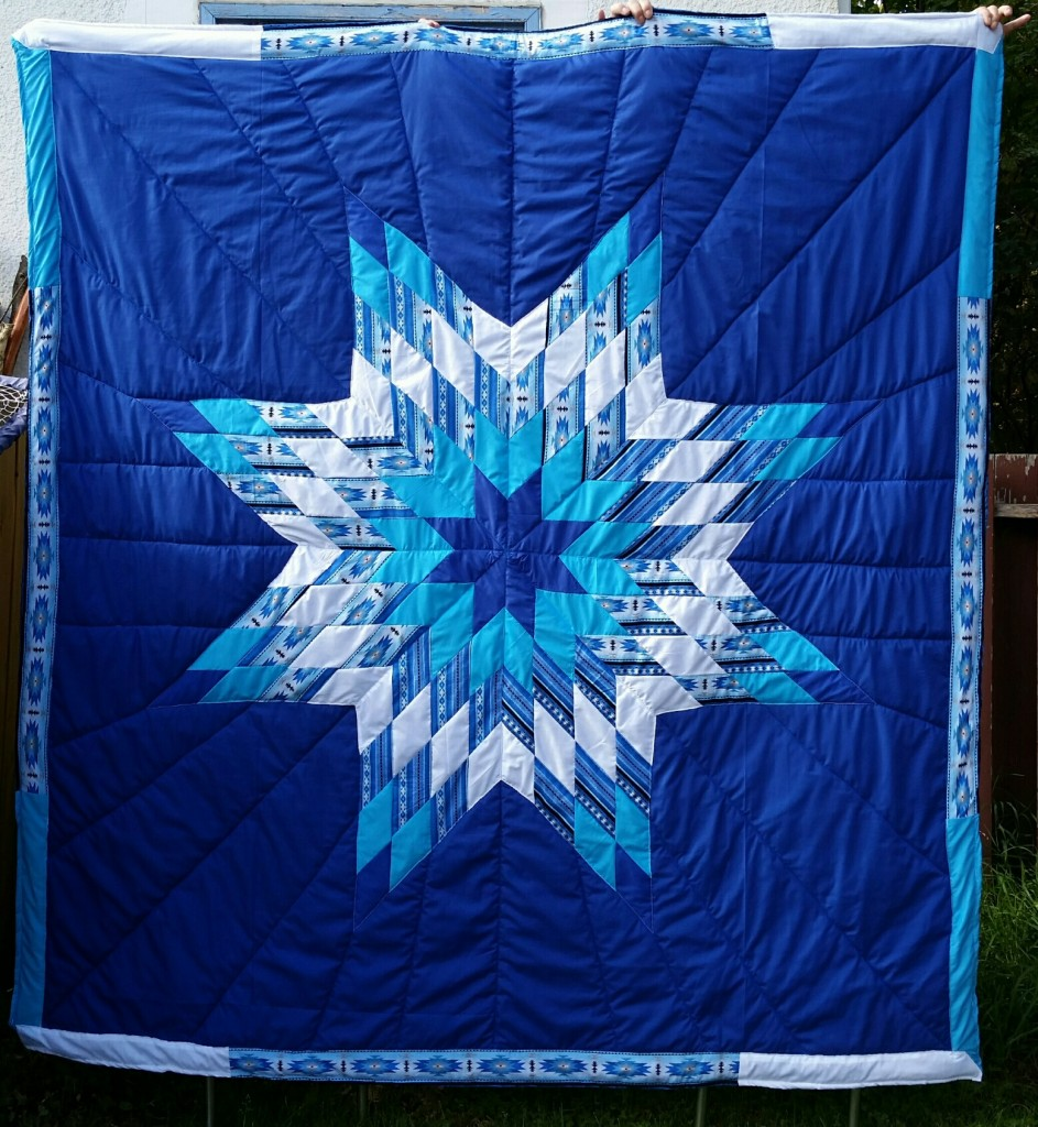 Dark blue blanket with white, turquoise, dark blue, and Navaho Print.