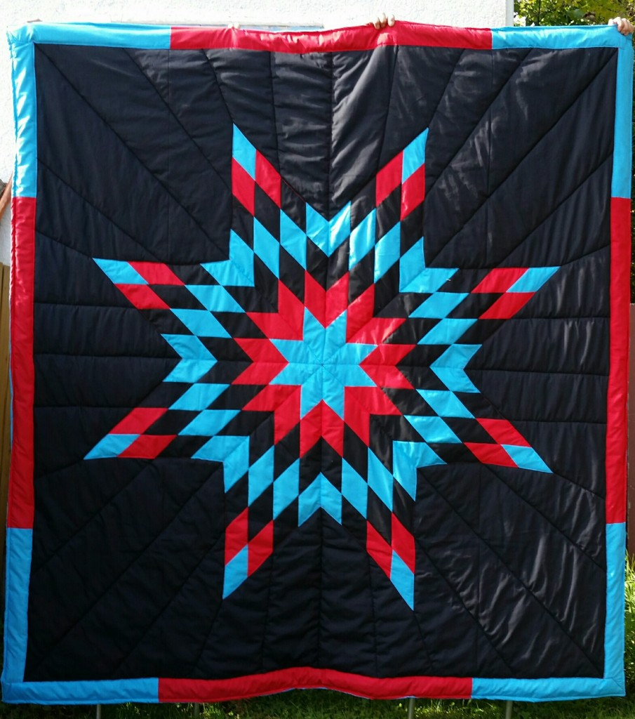 Black blanket with turquoise, red, and black star with border.