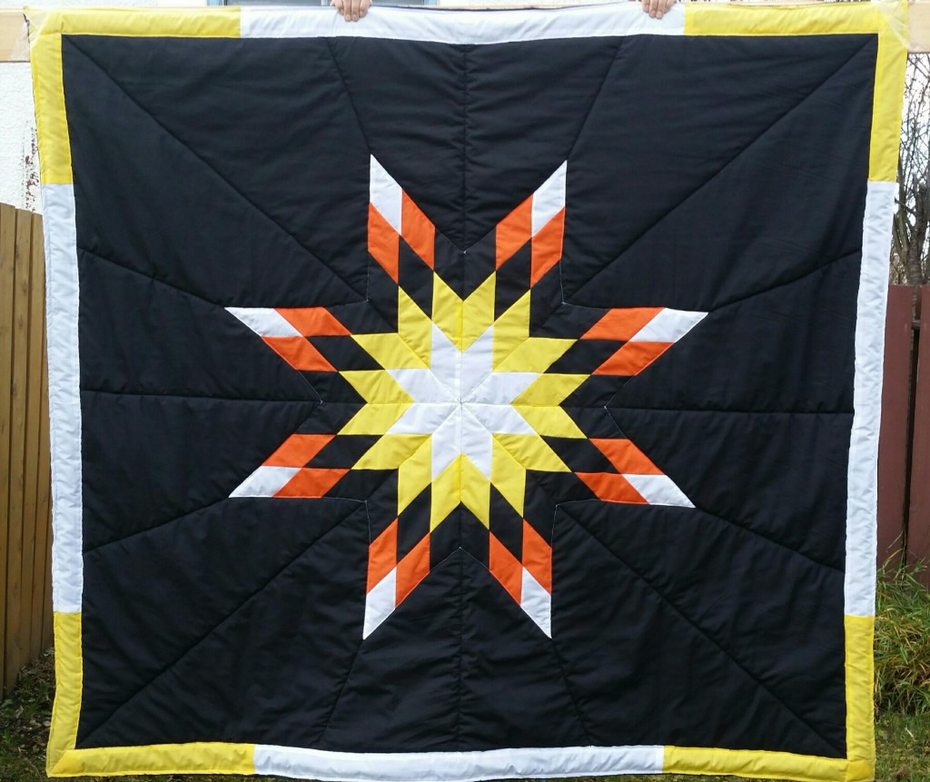 Black star blanket with orange, black, yellow and white star
