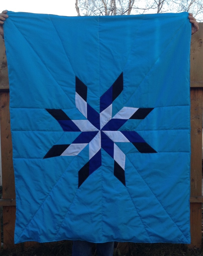 14. Turquoise blanket with black, dark blue, turquoise, and white star.