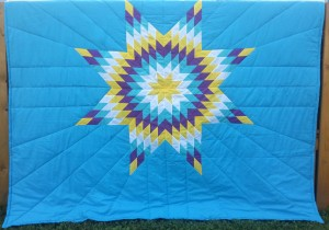 Light Blue Blanket with Yellow, White, Turquoise, Purple, and Yellow Star.