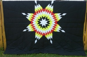Black blanket with white, black, yellow & red star.