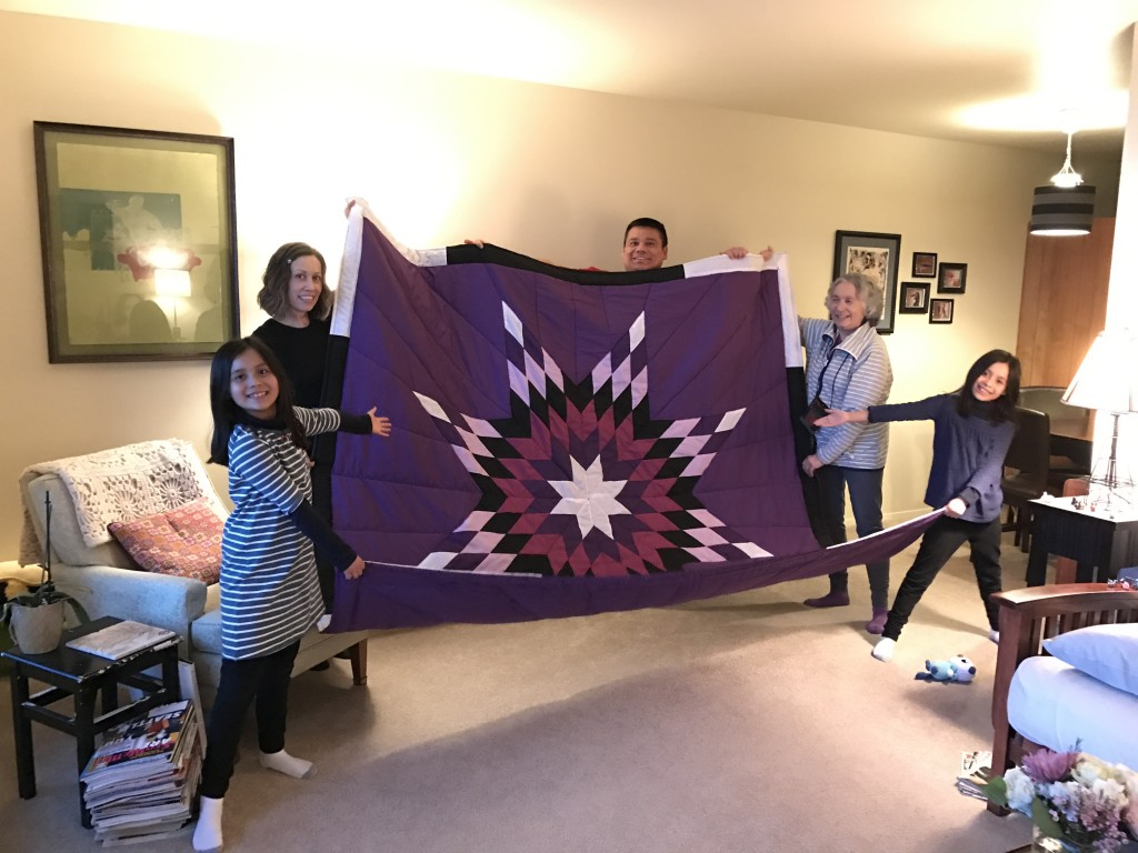 Timi Vann with her family and her mother holding the star blanket purchased from Cree Star Gifts