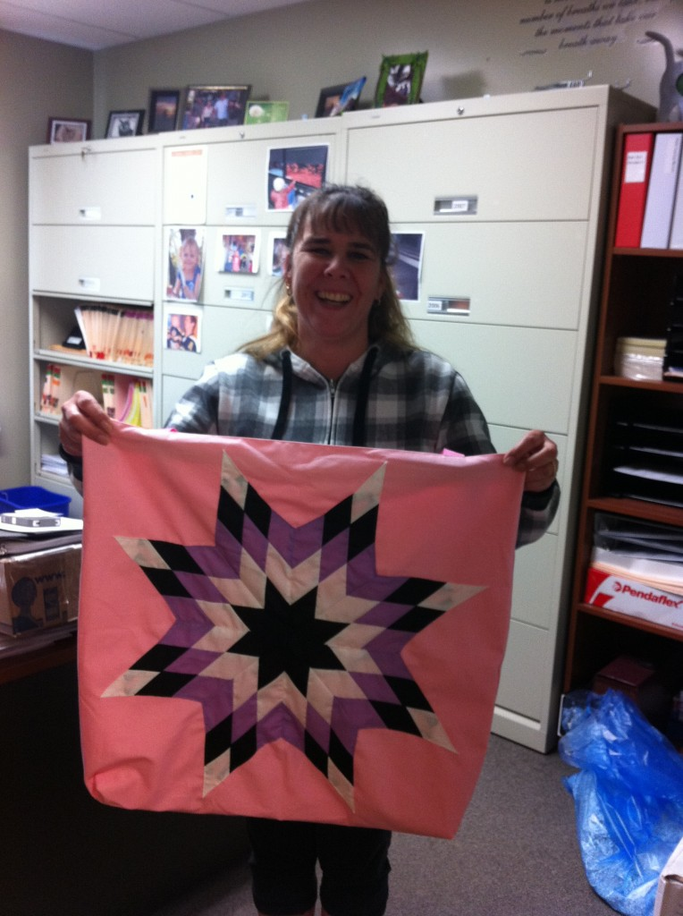 Deanna Brown (Program Administrative Assistant with the Public Health Unit of NITHA), holding a Star Bag purchased from Cree Star Gifts