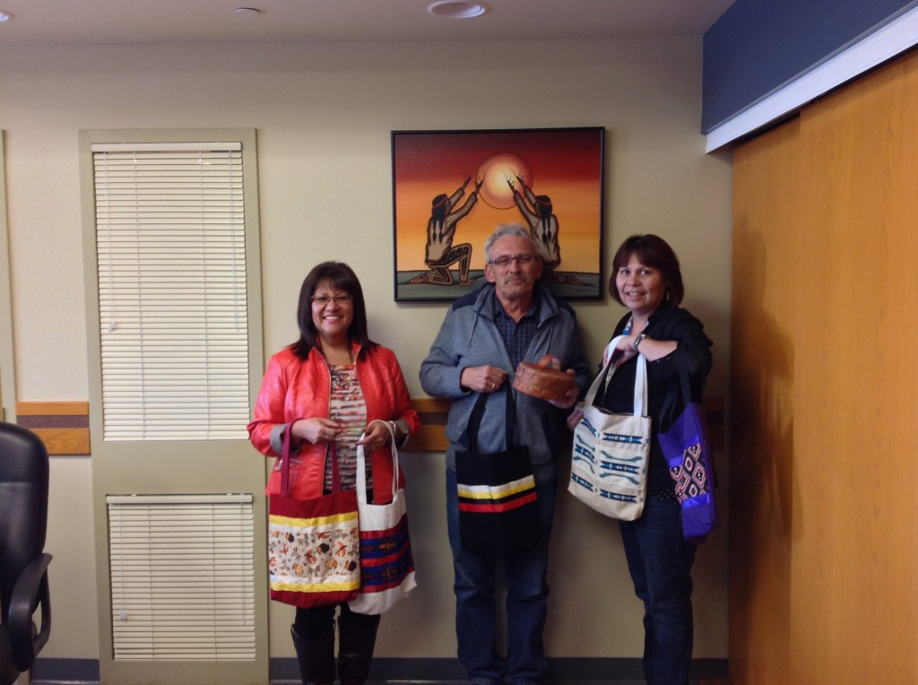 Photo: Leading Thunderbird Lodge 2014 From Left to Right: Karen Main (Executive Director), Kelly Pasloski (Educational Assistant), and Deborah McLean (Clinical Supervisor). They are holding a Small Birch Bark Basket, and Seminar Bags purchased from Cree Star Gifts.