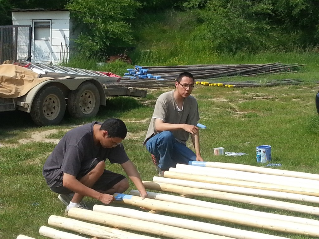 Devereaux & Dylan Roy painting bottom of teepee poles.
