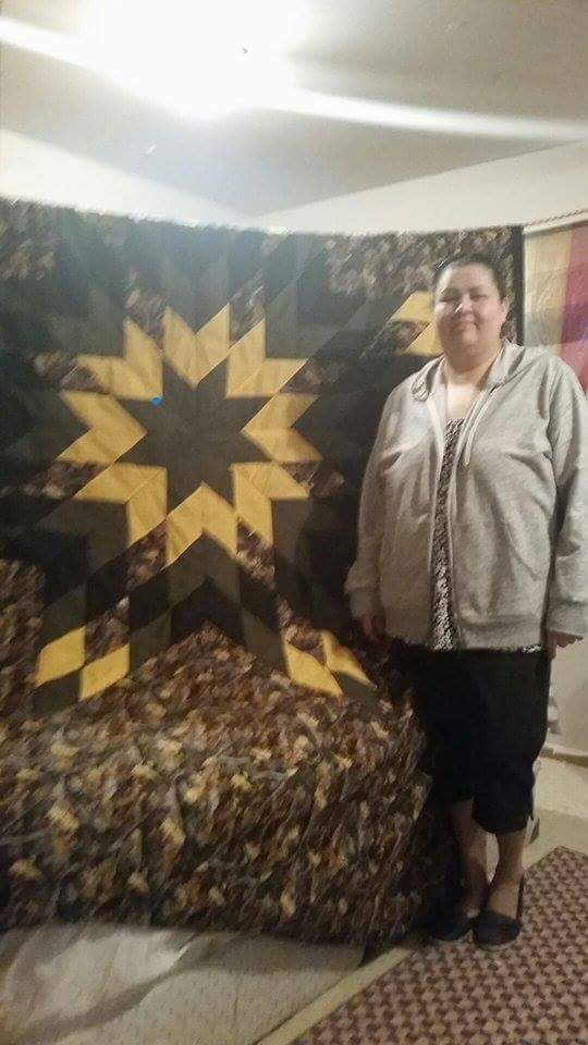 Alice George standing beside the custom camouflage blanket we created for her.