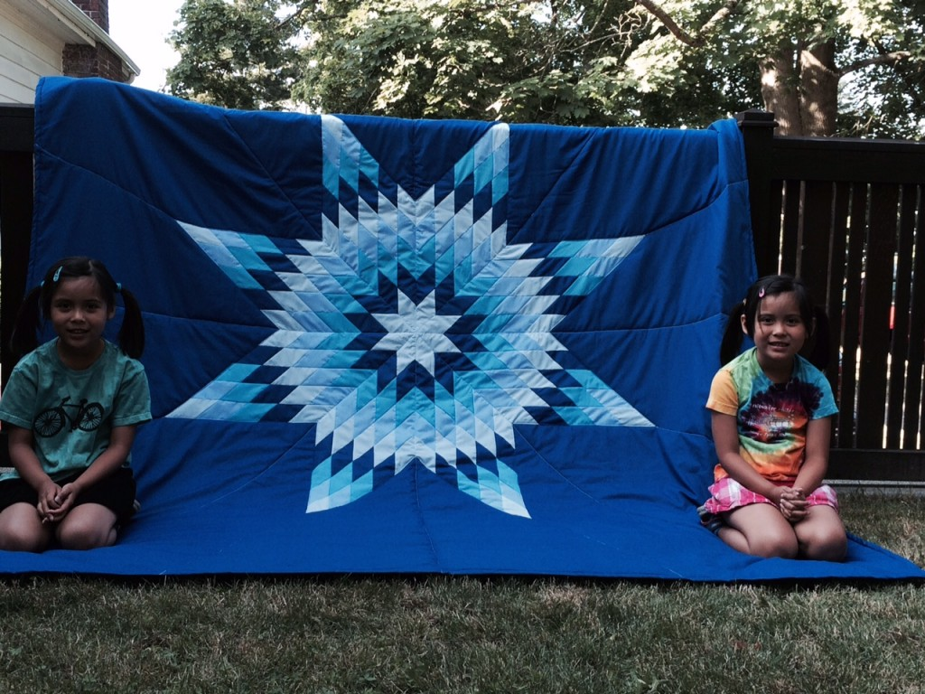 Timi's twins sitting in front of Star Blanket purchased from Cree Star Gifts.