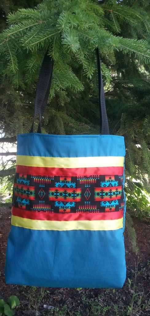 Turquoise bag with print and red and yellow ribbon