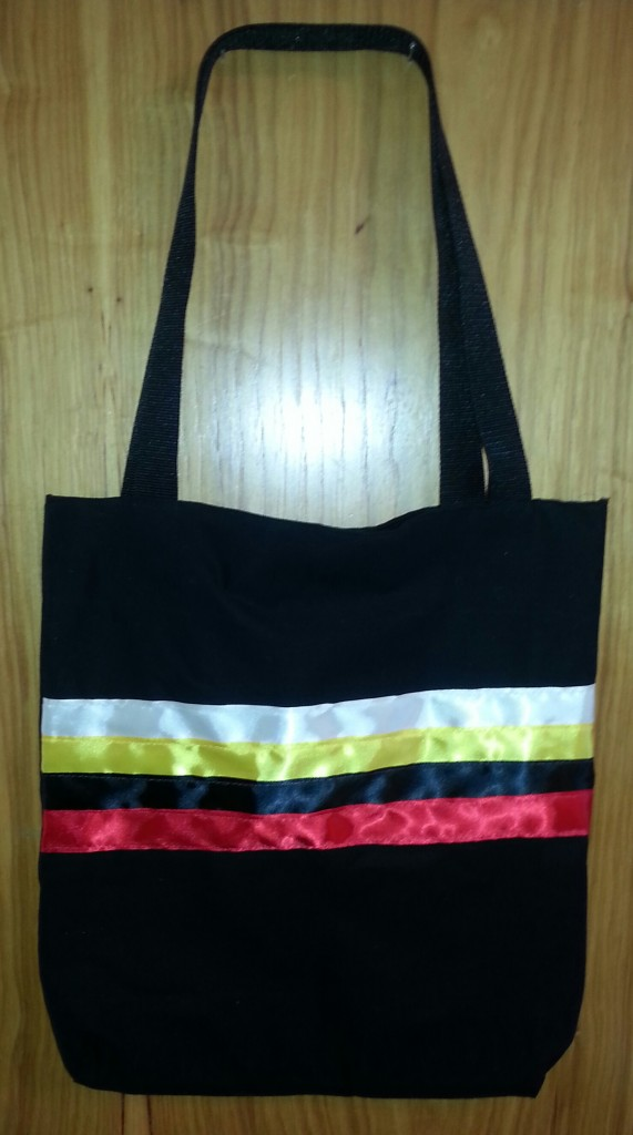 5. Black Bag with White, Yellow, Black and Red Ribbon across the front.